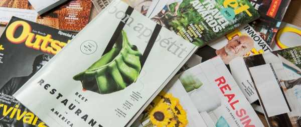 A variety of magazines are pictured. They are laying haphazardly in a pile.