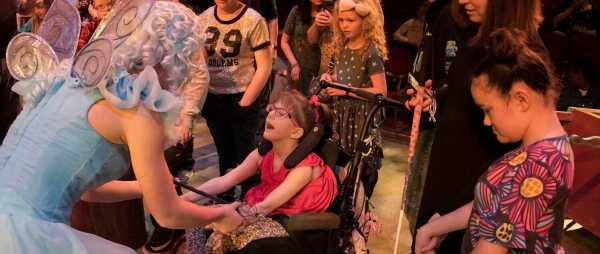 A little girl in a wheelchair is reaching out and holding hands with an actress. The Actress is dressed as a fairy, and has a blue dress, wings, and curly blonde hair.