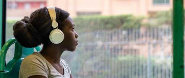 An african-american woman sits in front of a window. She is wearing headphones and looking out into the distance.
