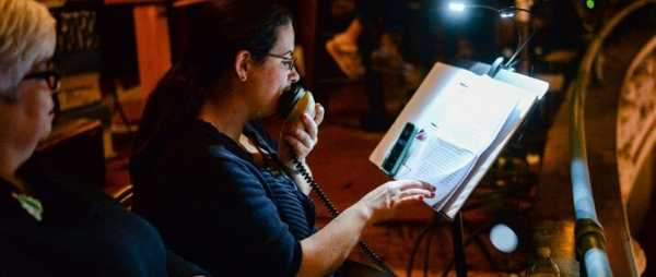 A woman is sitting in a darkened room. She is speaking into a microphone. She reads from a script, which is on a music stand in front of her. The script is illuminated by a small reading light.